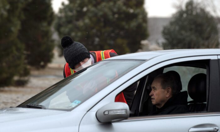 A health worker with the Colorado Department of Health and Environment talks with a man who is waiting for a drive-up testing site for the CCP virus to open in Denver, Colo. on March 13, 2020. (Jason Connolly/AFP via Getty Images)