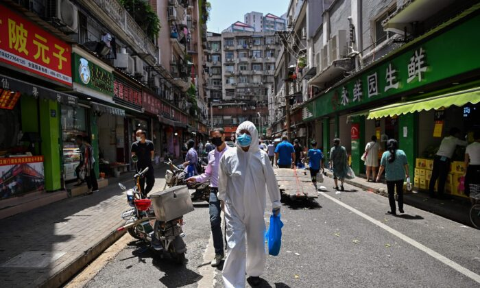 A man wearing protective gear walks past shops in Wuhan, in China's central Hubei Province on May 18, 2020. (Hector Retamal/AFP via Getty Images)