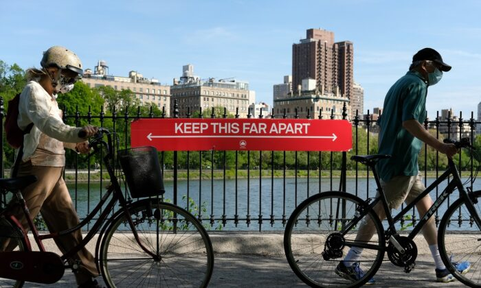 "People wearing protective masks walk their bicycles past a social distancing sign reading ""Keep This Far Apart"" at Jacqueline Kennedy Onassis Reservoir in Central Park in New York City on May 17, 2020. (Dia Dipasupil/Getty Images)"