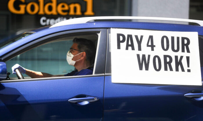 A driver wears a face mask and gloves during a caravan protest calling for California to enforce the AB5 law, in Los Angeles on April 16, 2020. (Mario Tama/Getty Images)