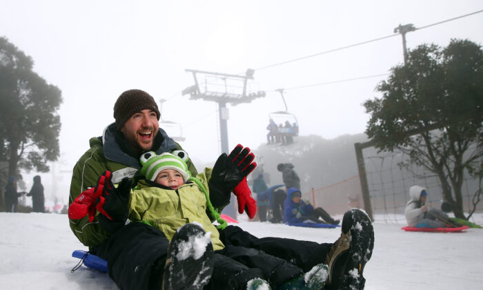 Dad and son snow play on the toboggan on July 11, 2015 in Mount Buller, Australia. (Robert Cianflone/Getty Images)