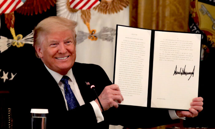 President Donald Trump holds up a copy of an executive order he signed on DOT deregulation, during a meeting with his cabinet in the East Room of the White House on May 19, 2020. (Alex Wong/Getty Images)