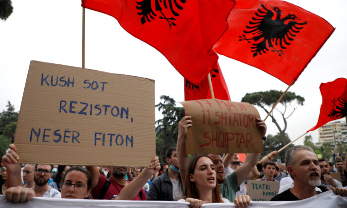 "A woman holds a sign reading ""Who resists today wins tomorrow"" as she attends a protest against the demolition of the National Theatre, during the outbreak of the coronavirus disease (COVID-19), in Tirana, Albania May 18, 2020. (Florion Goga/Reuters)"
