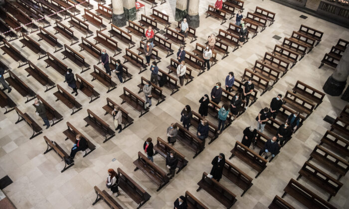 Faithful sitting in the benches, following the rules of social distancing, during a mass, the first day the presence of faithful was allowed during masses, in Turin, Italy, Monday, May 18, 2020. (Marco Alpozzi/LaPresse via AP)