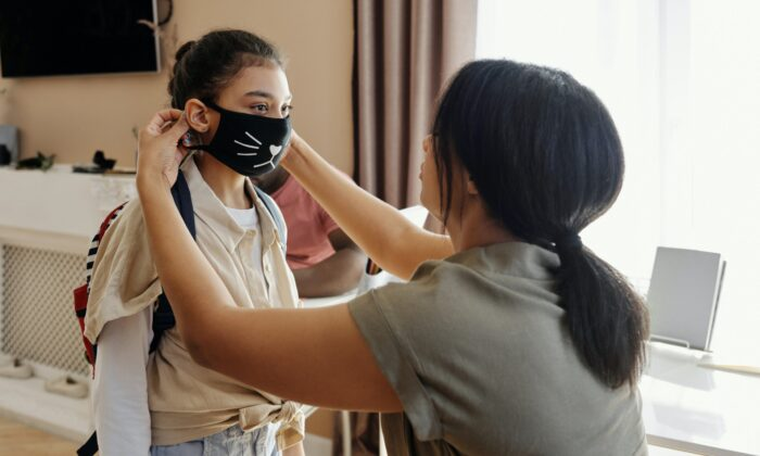 A file photo of a mother putting a mask on a child. A new mental-health screening program in Orange County is working with schools to identify students who may need help. (August de Richelieu/Pexels)