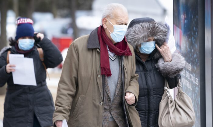 An elderly couple waits in a lineup outside a walk-in COVID-19 test clinic in Montreal on March 23, 2020. (The Canadian Press/Paul Chiasson)