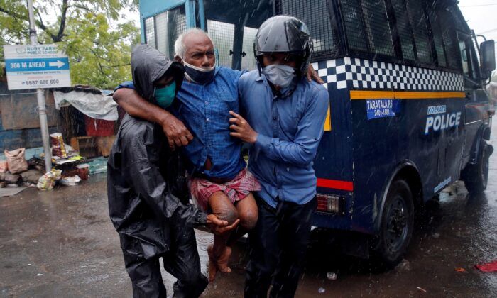 Police officers carry a disabled man to a safer place following his evacuation from a slum area before Cyclone Amphan makes its landfall, in Kolkata, India, on May 20, 2020. (Rupak De Chowdhuri/Reuters)