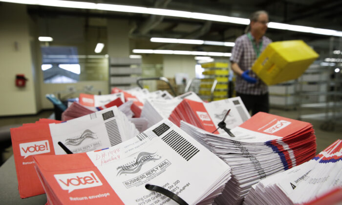 Empty envelopes of opened vote-by-mail ballots for the presidential primary are stacked on a table at King County Elections in Renton, Wash., on March 10, 2020. (Jason Redmond/AFP via Getty Images)