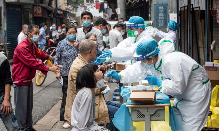 Medical workers take swab samples from residents to be tested for the COVID-19 coronavirus, in a street in Wuhan in China's central Hubei province on May 15, 2020.(STR/AFP via Getty Images)