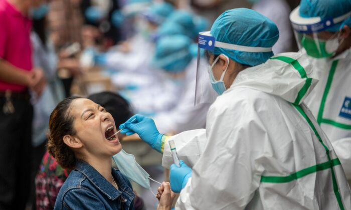 A medical worker takes a swab sample from a resident to be tested for the CCP virus in Wuhan, China on May 15, 2020. (STR/AFP via Getty Images)