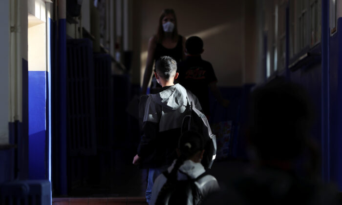 A student walks inside a francophone primary school during its reopening in Jumet, as a small part of Belgian children head back to their schools with new rules and social distancing measures, during the outbreak of the CCP virus in Jumet, Belgium, on May 18, 2020. (Yves Herman/Reuters)