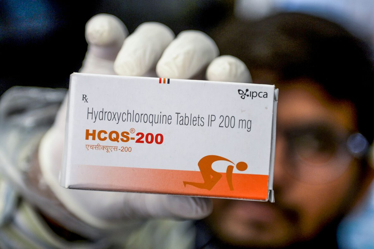 A pharmacist displaying a box of hydroxychloroquine