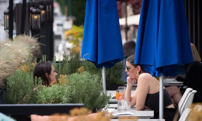 Two women have drinks on the patio at an Earls restaurant, in Vancouver, on May 19, 2020. British Columbia began phase two of the reopening of its economy Tuesday, allowing certain businesses that were ordered closed due to COVID-19 to open their doors to customers if new health and safety regulations are followed. (Darryl Dyck/The Canadian Press)