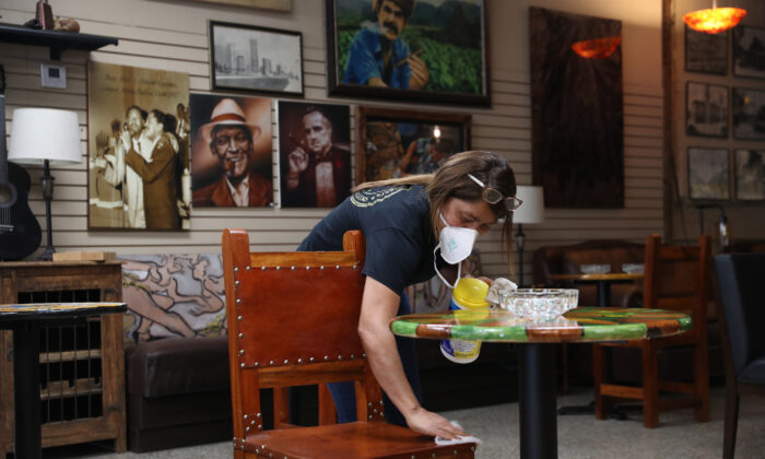 A woman cleans a table and chairs in a cigar shop in Miami, Fla. on May 19, 2020. (Joe Raedle/Getty Images)