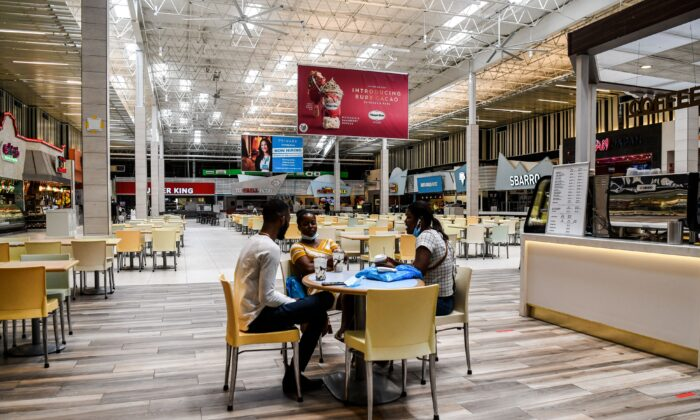People eat in a deserted food court inside a mall west of Fort Lauderdale, Fla., on May 18, 2020. (Chandan Khanna/AFP via Getty Images)