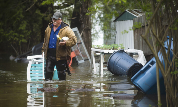 A man brings a chair to the front of his house from the back yard, wading through floodwater in Edenville, Mich., on May 19, 2020. (Katy Kildee/Midland Daily News via AP)