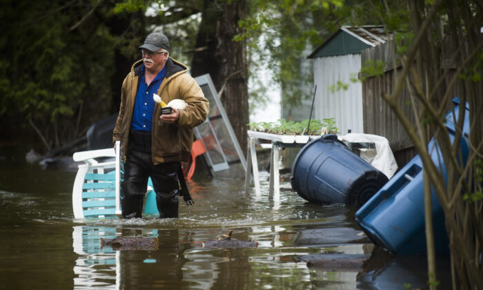 Mark Musselman brings a chair to the front of his house from the back yard, wading through floodwater, Tuesday, May 19, 2020 in Edenville, Mich. (Katy Kildee/Midland Daily News via AP)