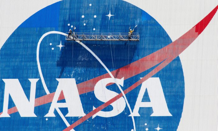 Workers pressure wash the logo of NASA on the Vehicle Assembly Building before SpaceX will send two NASA astronauts to the International Space Station aboard its Falcon 9 rocket, at the Kennedy Space Center in Cape Canaveral, Fla., U.S., May 19, 2020. (Joe Skipper/Reuters)