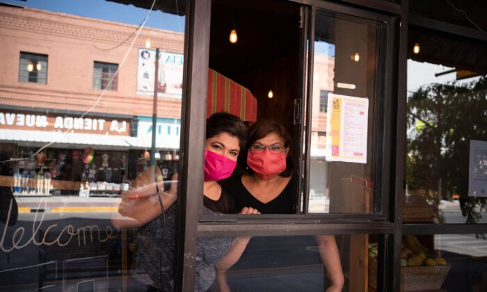 Vanessa Zubia-Meza and her mother Margie Zubia are pictured in the window of their new restaurant called El Paseo in downtown El Paso, Texas on May 18, 2020. (Paul Ratje/AFP via Getty Images)