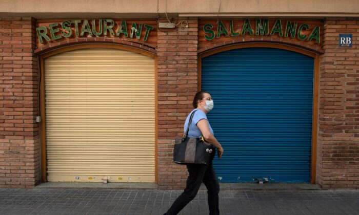 A woman wearing a face mask walks past a closed restaurant in Barcelona on May 13, 2020, during the national lockdown to prevent the spread of the COVID-19 disease. - Spain is to restrict arrivals from Europe's Schengen zone and impose a mandatory 14-day quarantine period on all travellers to avoid importing new virus cases, the government said yesterday. Both measures come into effect on May 15, 2020 and will remain in force until May 24 when the state of emergency expires -- or beyond if the measure is extended, the official government bulletin said. (Photo by Josep LAGO / AFP) (Photo by JOSEP LAGO/AFP via Getty Images)