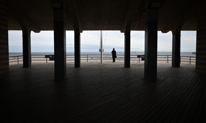 A man wearing a mask stands at the promenade at Coney Island Beach in New York City on May 18, 2020. (Johannes Eisele/AFP via Getty Images)