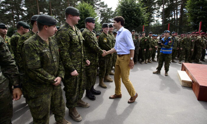 Prime Minister Justin Trudeau shakes hands with Canadian troops after delivering a speech at the Adazi Military Base in Kadaga, Latvia, on July 10, 2018. (Sean Kilpatrick/The Canadian Press)