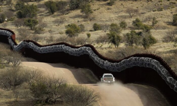 A Customs and Border Control agent patrolling on the U.S. side of a razor-wire-covered border wall along the Mexico east of Nogales, Ariz., on March 2, 2019. (Charlie Riedel/AP Photo)