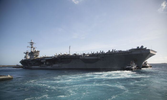 The aircraft carrier USS Theodore Roosevelt (CVN 71) departs Apra Harbor following an extended visit to Guam in the midst of the COVID-19 global pandemic, in an undated file photo. (U.S. Marine Corps photo by Staff Sgt. Jordan E. Gilbert)