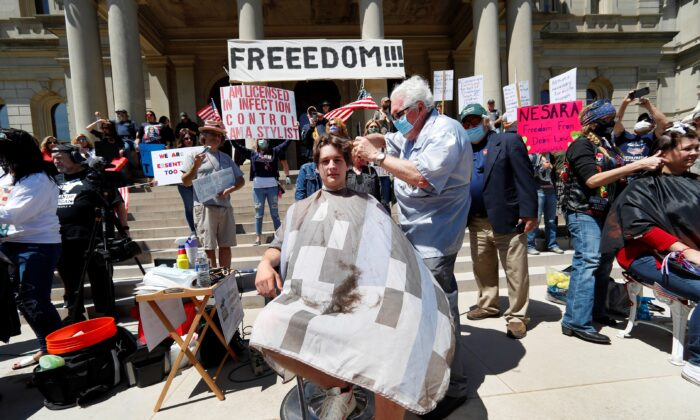 The media record barber Karl Manke, of Owosso, giving a free haircut to Parker Shonts on the steps of the State Capitol during a rally in Lansing, Mich., on May 20, 2020. (Paul Sancya/AP Photo)