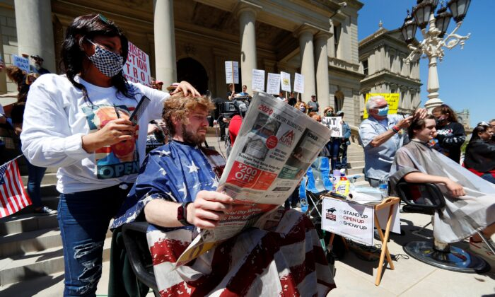 Jody Hebberd, left, gives a free haircut to Reid Scott, as he reads the paper on the steps of the State Capitol as Karl Manke, right, cuts the hair of Parker Shonts during a rally in Lansing, Mich., on May 20, 2020. (Paul Sancya/AP Photo)