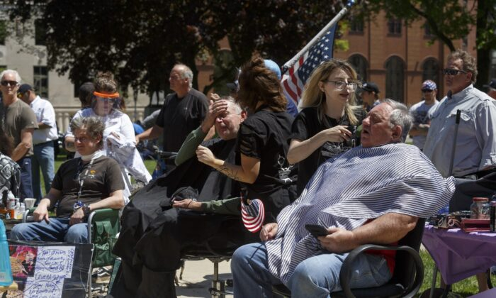 Barbers cut hair for free near the steps of the state Capitol during Operation Haircut in Lansing, Mich., on May 20, 2020. (Elaine Cromie/Getty Images)