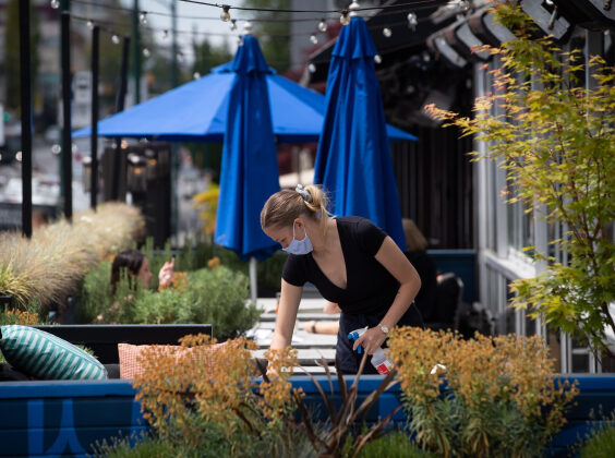A server wears a face mask while cleaning a table on the patio at an Earls restaurant, in Vancouver, on May 19, 2020. (Darryl Dyck / The Canadian Press)