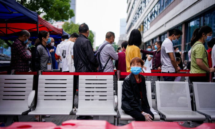 A woman wearing a face mask looks on in front of others standing in a queue for nucleic acid testings in Wuhan, the Chinese city hit hardest by the coronavirus disease (COVID-19) outbreak, Hubei province, China May 16, 2020. (Aly Song/Reuters)