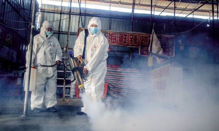 Two volunteers are spraying disinfectant at a market in the border city of Suifenhe in China's northeastern Heilongjiang province on May 6, 2020. (STR/AFP via Getty Images)