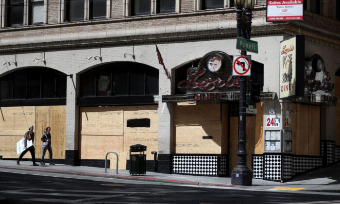 Pedestrians walk by a boarded-up restaurant in San Francisco on March 31, 2020. (Photo by Justin Sullivan/Getty Images)