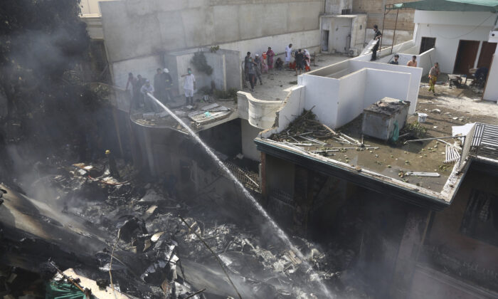 Fire brigade staff try to put out fire caused by plane crash in Karachi, Pakistan, on May 22, 2020. (Fareed Khan/AP Photo)
