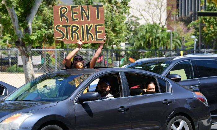Demonstrators call for a rent strike during the COVID-19 pandemic as they pass City Hall in Los Angeles, Calif., on May 1, 2020. (Frederic J. Brown/AFP via Getty Images)