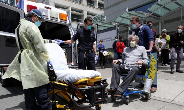 Ronald Temko, sitting, a COVID-19 patient, prepares to be loaded into an ambulance after discharge from the UCSF Medical Center at Mount Zion in San Francisco, Calif., on May 20, 2020. (Justin Sullivan/Getty Images)