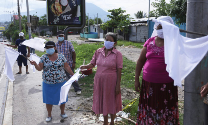 Residents of the Las Victorias neighbourhood, most of them informal sellers, wave white flags as a sign asking for food, since the government suspended the movement of people due to the coronavirus disease (COVID-19) outbreak, in Soyapango, El Salvador May 19, 2020. (Victor Pena/Reuters)