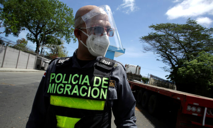 An immigration officer walks near trucks parked in a queue at the border between Costa Rica and Nicaragua, after Nicaragua's government closed the border for freight traffic, during the outbreak of the CCP virus (COVID-19), in Penas Blancas, Costa Rica on May 21, 2020. (Juan Carlos Ulate via Reuters)