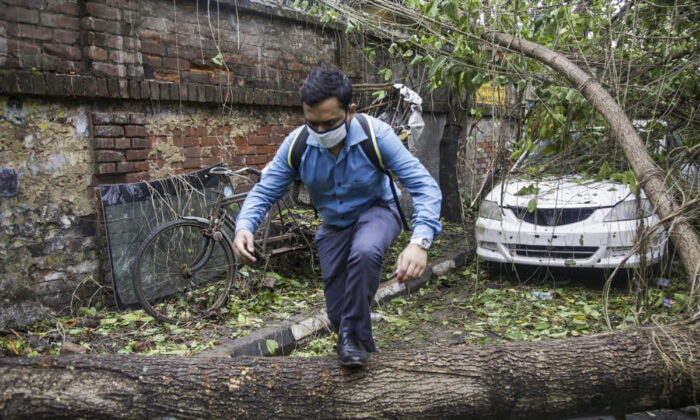 A man makes his way past a tree fallen in the middle of a road after Cyclone Amphan hit the region in Kolkata, India, Thursday, May 21, 2020. (Bikas Das/AP)
