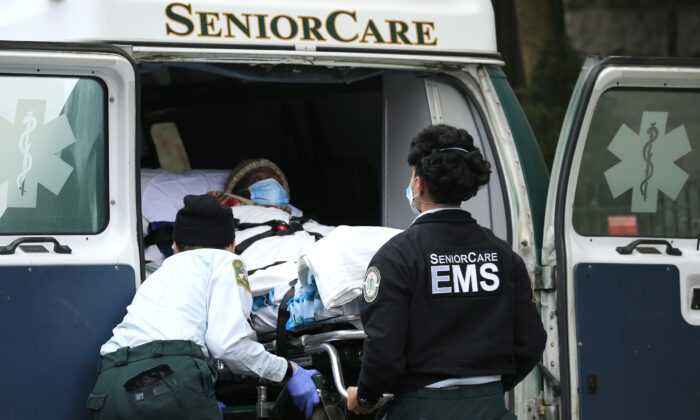 Emergency Medical Service workers unload a patient out of their ambulance at the Cobble Hill Health Center in the Cobble Hill neighborhood of the Brooklyn borough of New York City on April 18, 2020. (Justin Heiman/Getty Images)