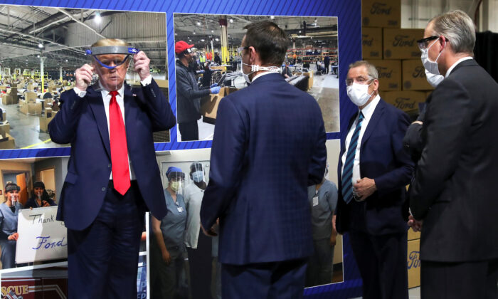 President Donald Trump holds up a protective face shield as Ford Motor Company executives wearing face masks look on during a tour of the Ford Rawsonville Components Plant that is manufacturing ventilators, masks and other medical supplies during the CCP virus pandemic in Ypsilanti, Mich., on May 21, 2020. (Leah Millis/Reuters)