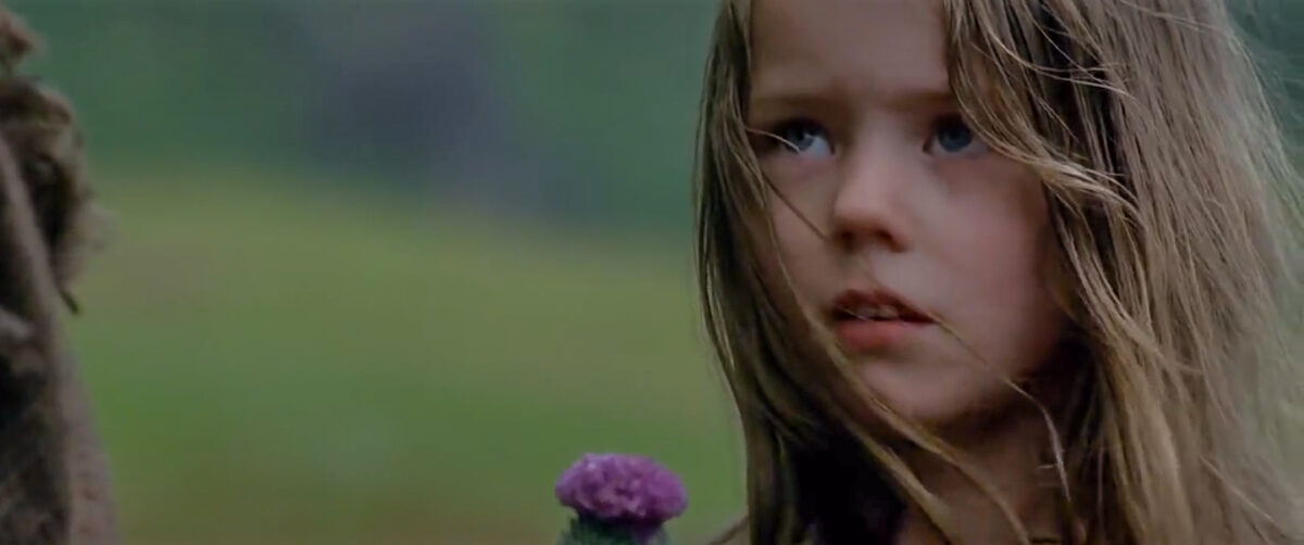 """young girl holds purple thistle in """"Braveheart"""""""