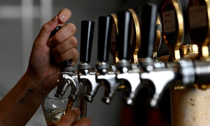 A bartender pours a glass of beer for a customer at a restaurant in Sydney, Australia, on May 15, 2020. (Saeed Khan/ AFP via Getty Images)