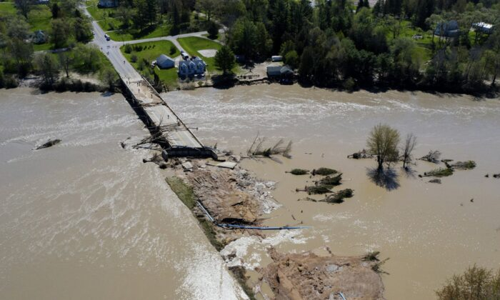 People survey the flood damage to the Curtis Road Bridge in Edenville, Mich., on May 20, 2020. (Neil Blake/The Grand Rapids Press via AP)
