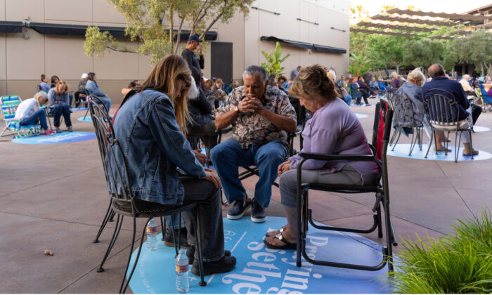 A family prays together in the courtyard of Calvary Chapel Chino Hills during the COVID-19 pandemic in Chino Hills, Calif. (Courtesy of Calvary Chapel Chino Hills)