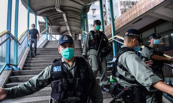 Riot police set up a cordon near a group of pro-democracy protesters (not pictured) during their route from outside the Western Police Station to the Chinese Liaison Office in Hong Kong on May 22, 2020. (Anthony Wallace/AFP via Getty Images)