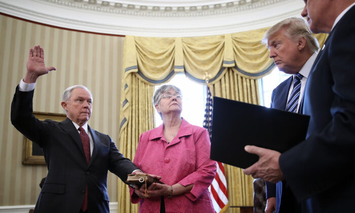 President Donald Trump watches as Jeff Sessions, left, is sworn in as the new Attorney General by Vice President Mike Pence, right, in the Oval Office of the White House in Washington February 9, 2017. Also pictured is Sessions's wife, Mary,, holding the Bible. (Win McNamee/Getty Images)