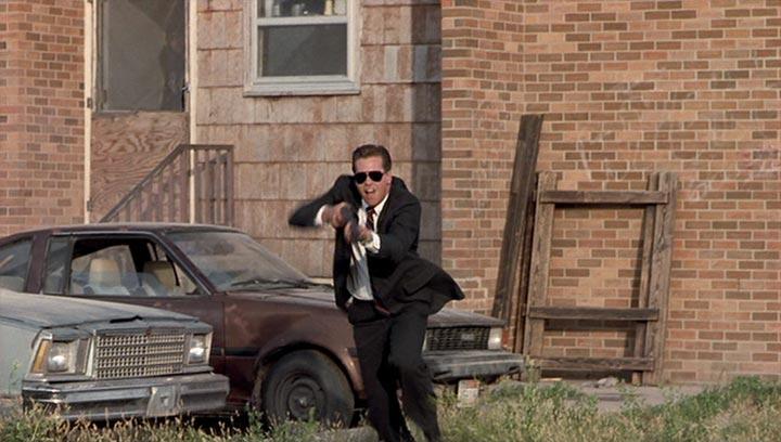 man in black suit with gun